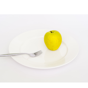 Portion Sizes vs. Serving Sizes: What You're Eating and What You Should be Eating: Apple and fork on white plate: No More Excuses Fitness Training: www.nmefitnesstraining.com